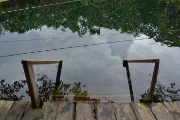 Stair leading into the water at cenote in Tulum